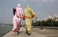 <p>Two women walk along an embankment, as a poster of President Barack Obama is seen in the distance, in Mumbai November 6, 2010. Obama is arriving for a four-day visit to India. REUTERS/Jim Young</p>