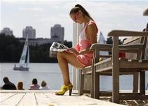 <p>A model reads a magazine during the summer contingent of the Millionaire Fair of luxury goods in Moscow, July 4, 2010. REUTERS/Sergei Karpukhin</p>