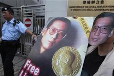 <p>A pro-democracy protester wearing a mask of jailed Chinese democracy activist Liu Xiaobo and holding a picture of Liu attends a protest urging for the release of Liu and political prisoners, outside the Chinese liaison office in Hong Kong October 11, 2010. REUTERS/Tyrone Siu</p>