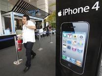 <p>Foto de archivo de un hombre frente a un anuncio de un iPhone 4 en una tienda de Bangkok, sep 24 2010. Los fabricantes de equipos de telecomunicaciones se abren paso para vender y promocionar su tecnología inalámbrica de nueva generación, pero queda sin responder la pregunta ¿Están construyendo demasiada capacidad en un momento en el que la demanda no existe? REUTERS/Chaiwat Subprasom</p>