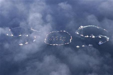 Commercial fishermen and other mariners form the word ''SOS'' during an event held to spread the message of saving the oceans from acidification caused by fossil fuel emissions, in Homer, Alaska, September 6, 2009. REUTERS/Lou Dematteis