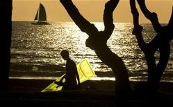 <p>A tourist carries an inflatable raft while walking against the setting sun on Waikiki Beach in Honolulu, Hawaii, January 2, 2010. REUTERS/Larry Downing</p>