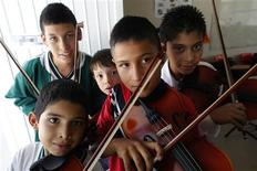 <p>10-year old Jose Angel (R) and his classmates pose for a photograph with their violins at their school in Ciudad Juarez, October 13, 2010. REUTERS/Tomas Bravo</p>
