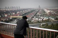 <p>A man watches the Huaxi village, at Jiangsu province December 2, 2010. REUTERS/Carlos Barria</p>