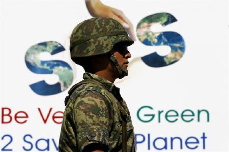 A soldier guards the venue of U.N. climate talks in Cancun December 10, 2010. REUTERS/Jorge Silva