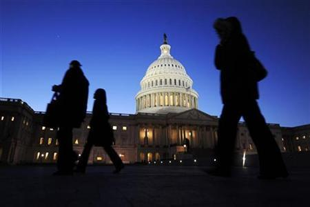 Staff members walk past the US Capitol dome in Washington, February 24, 2009. REUTERS/Jonathan Ernst