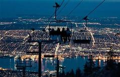 <p>Snowboarders ride a chair lift on one of the many snow runs during night skiing on Grouse Mountain with the city of Vancouver, British Columbia down below February 12, 2009. REUTERS/Andy Clark</p>