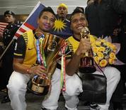 <p>Capitão da Malásia, Safiq Bin Rahim (esq) com o troféu da Copa Suzuki e seu colega Safee Sali, no aeroporto em Sepang, Malásia. A Malásia comemorou uma vitória rara no futebol regional, declarando um feriado público. 30/12/2010 REUTERS/Bazuki Muhammad /Arquivo</p>