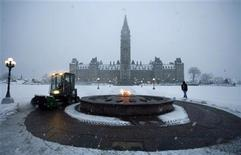 <p>A worker cleans away snow around the Centennial Flame on Parliament Hill in Ottawa November 21, 2007. REUTERS/Christopher Pike</p>