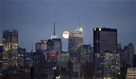 <p>A full moon rises behind the skyline of midtown Manhattan in New York, November 21, 2010. REUTERS/Gary Hershorn</p>