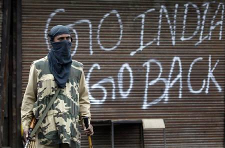 An Indian policeman stands guard near a closed shop during a curfew in Srinagar September 14, 2010. REUTERS/Danish Ismail/Files