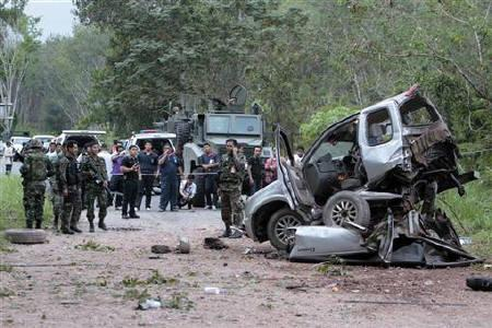 Security personnel investigate the site of an attack in Thailand's southern Yala province January 25, 2011. A powerful roadside bomb killed nine civilians in Thailand's restive deep south on Tuesday, an attack blamed on separatist insurgents, police said. REUTERS/Surapan Boonthanom