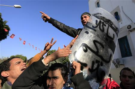 A protester chants slogans as he holds a riot police shield during clashes with the police near government offices in the Casbah, the old city of Tunis, January 26, 2011. REUTERS/Zohra Bensemra