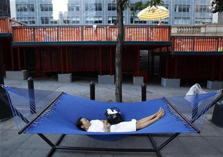 A woman rests in a hammock waiting for her chance to swim in one of three converted dumpster pools on Park Avenue in New York August 7, 2010. REUTERS/Shannon Stapleton