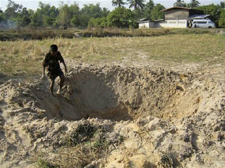 A Thai man is seen at a crater allegedly caused by a shell in Si Sa Ket province near the 11th-century Preah Vihear temple at the border between Thailand and Cambodia February 5, 2011. Deadly fighting broke out between Thai and Cambodian soldiers on Friday and Saturday. REUTERS/Stringer