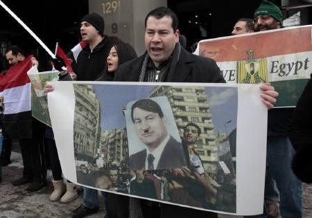 Egyptian-American Hany Othman holds a sign with a picture of Egypt's President Hosni Mabarak depicted as Adolf Hitler as he demonstrates in support of the anti-Mubarak protesters in Egypt in Royal Oak, Michigan February 5, 2011. REUTERS/Rebecca Cook