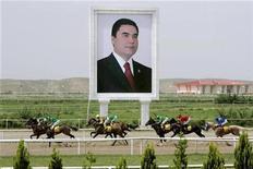 <p>Horses race past a giant portrait of Turkmen President Kurbanguly Berdymukhamedov at the presidential race track in Ashgabat May 11, 2007. RETUERS/ITAR-TASS/PRESIDENTIAL PRESS SERVICE</p>