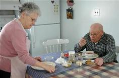 <p>Germaine Levesque (L) lays a plate on her kitchen table in Canada while her husband, Edmond Levesque (R) eats his soup across the international border in the United States of America on the other side of the table, in the town of Estcourt, Maine on March 27, 2006. REUTERS/STR New</p>