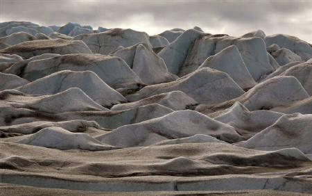 The Greenland ice cap is formed into mounds and ridges near the town of Kulusuk August 2, 2009.  REUTERS/Bob Strong/Files