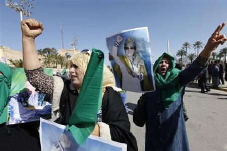 Pro-government supporters hold posters of Libyan leader Muammar Gaddafi as they chant slogans during a demonstration in Tripoli February 17, 2011. REUTERS/Ismail Zitouny