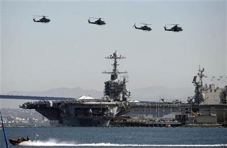 Crowds aboard the aircraft carrier USS John C. Stennis watch as U.S. Navy helicopters fly past the ship February 12, 2011 in San Diego. REUTERS/Denis Poroy
