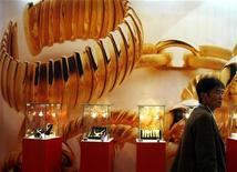 <p>A visitor to the China International Jewellery Fair walks past a poster and gold jewellery display in Beijing November 12, 2008. Chinese investors are still spending much less on gold than Chinese jewellery buyers. REUTERS/David Gray</p>