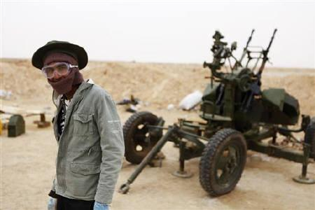 A Libyan rebel stands near an anti-aircraft gun at a checkpoint outside the city of Ajdabiyah, March 13, 2011. REUTERS/Finbarr O'Reilly