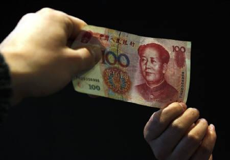 A shop owner exchanges a Chinese yuan banknote with a customer in central Beijing April 13, 2010. REUTERS/David Gray/Files