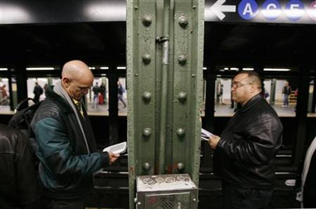 A man reads on a Kindle while waiting for the subway in New York October 14, 2009. REUTERS/Lucas Jackson