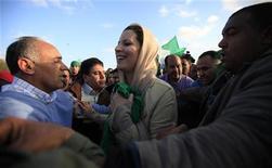 <p>Aisha Gaddafi, daughter of Libya's leader Muammar Gaddafi, smiles as she is greeted by supporters at Bab Al-Aziziyah in Tripoli March 19, 2011. REUTERS/Zohra Bensemra (LIBYA - Tags: POLITICS CIVIL UNREST)</p>