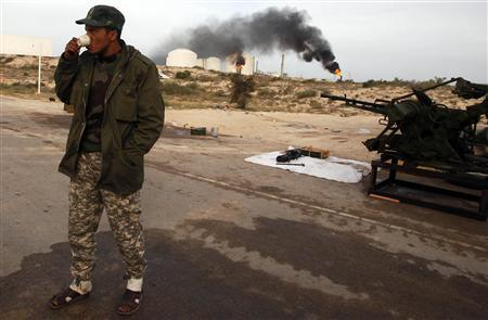 A rebel drinks coffee inside an oil terminal compound after it was retaken by rebels in Zueitina, 850 km (528 miles) east of Tripoli, March 27, 2011. REUTERS/Suhaib Salem