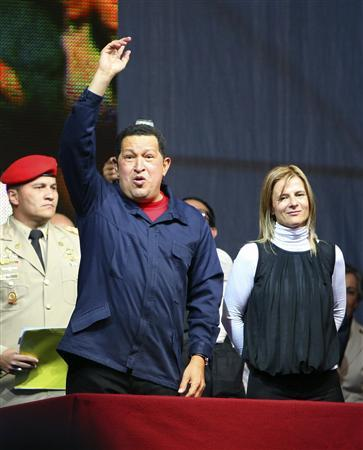 Venezuela's President Hugo Chavez waves to the crowd next to Florencia Saintout (R), Dean of the University of La Plata, after being awarded with the Rodolfo Walsh prize in La Plata March 29, 2011. Chavez, who critics accuse of stifling press freedom, was given a prize by an Argentine journalism school on Tuesday for his contribution to ''popular communication''. Since coming to power in 1999, Chavez has polarized his country and opponents say he has set out to silence criticism by refusing to renew the licenses of a critical broadcaster and dozens of radio stations. REUTERS/Pablo Busti