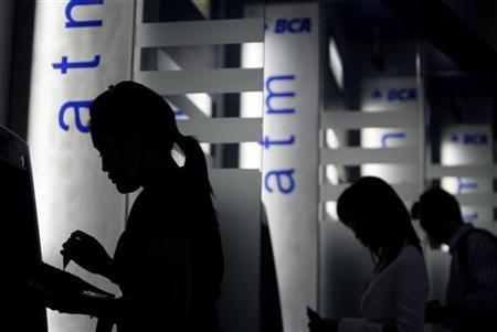 Costumers use BCA automated teller machines (ATMs) at BCA's headquarters in Jakarta February 3, 2010. REUTERS/Beawiharta