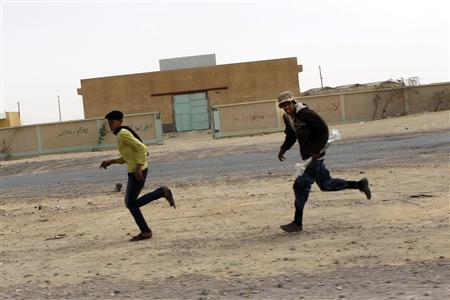 Rebel fighters take cover during a shelling along the road between Ajdabiyah and Brega March 30, 2011. REUTERS/Youssef Boudlal