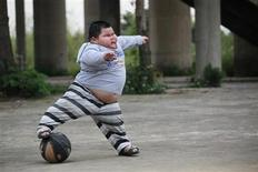 <p>Lu Zhihao, 4, kicks a ball at a basketball court in Foshan, Guangdong province March 28, 2011. REUTERS/Joe Tan</p>