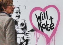 <p>Mulher passa por grafite do artista Rich Simmons, que representa a rainha Elizabeth, da Inglaterra, desenhando os nomes do príncipe William e Kate Middleton, em Londres. O casamento real vai ser celebrado no dia 29 de abril. 01/04/2011 REUTERS/Toby Melvill</p>