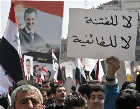 A pro-government demonstrator holds up a placard, which reads: ''No to strife, no to sectarianism'', during a rally at the central bank square in Damascus March 29, 2011. REUTERS/Wael Hmedan