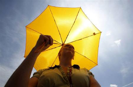 An activist  holds an umbrella during a demonstration outside the United Nations Building in Bangkok, September 29, 2009. REUTERS/Sukree Sukplang/Files