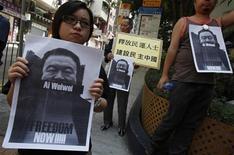 """<p>Manifestantes pró-democracia mostram retratos do artista chinês, Ai Weiwei, pedindo sua libertação, em Hong Kong, no domingo. O governo chinês afirmou nesta terça-feira que está """"descontente"""" com o apoio estrangeiro ao artista e ativista detido, após a prisão de Ai na semana passada. 10/04/2011 REUTERS/Bobby Yip</p>"""