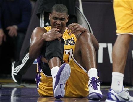 Los Angeles Lakers Andrew Bynum holds his knee after falling during the first half of their NBA basketball game against the San Antonio Spurs in Los Angeles, California, April 12, 2011. REUTERS/Lucy Nicholson