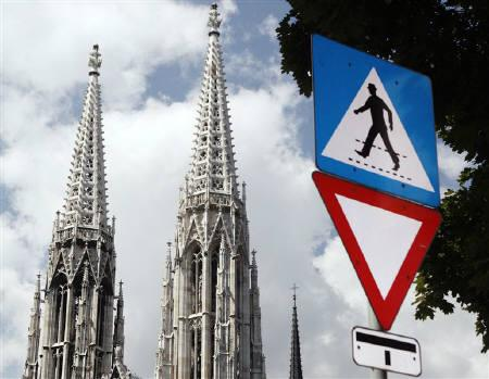 The towers of Votivkirche church are pictured behind traffic signs in Vienna August 10, 2010. REUTERS/Heinz-Peter Bader/Files