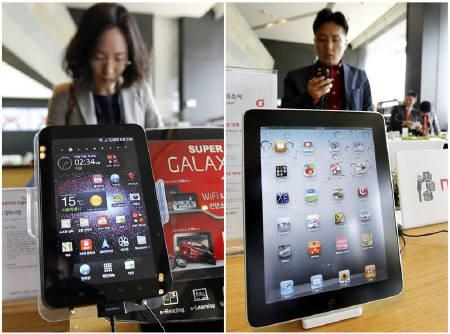 Customers look at smartphones behind Samsung Electronics' Galaxy Tab tablet (L) and Apple Inc's iPad tablet displayed at a registration desk at the headquarters of South Korean mobile carrier KT in Seoul, in this combination picture made April 19, 2011.  REUTERS/Jo Yong-Hak