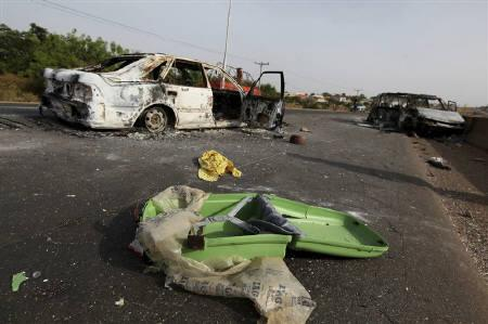 A broken suitcase is seen on a road near burnt vehicles, a day after election riots, in the Kaduna metropolis in northern Nigeria April 19, 2011. REUTERS/Afolabi Sotunde