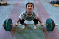 <p>A weight lifter practises during a training session at a provincial training base in Jinan, capital of east China's Shandong province July 9, 2007. REUTERS/Stringer</p>