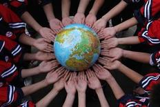 <p>Students pose for the photo with a globe during a campaign to mark the World Earth Day in a middle school in Dexing, Jiangxi province April 19, 2011. REUTERS/China Daily</p>
