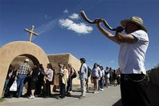 <p>Arthur Medina blows a horn as people wait in line to enter El Santuario de Chimayo in Chimayo, New Mexico April 22, 2011. Thousands of people walk to the little chapel over Easter weekend where, they believe, the dirt inside holds the power to heal, some from as far away as Mexico and Colorado. REUTERS/Jessica Rinaldi</p>