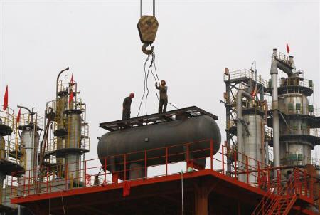 Labourers work on a refinery in Suining, Sichuan province October 22, 2009. REUTERS/Stringer/Files