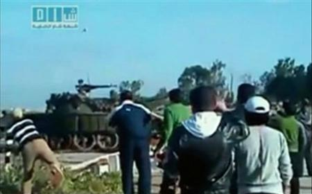 A crowd watches as a man throws a rock at a passing tank in a location given as Deraa in this still image from an amateur video on April 25, 2011. REUTERS/Social Media Website via Reuters TV