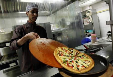 A cook slides a pizza onto a serving plate in the kitchen at a Pizza Hut restaurant in Mumbai, March 29, 2011. REUTERS/Danish Siddiqui