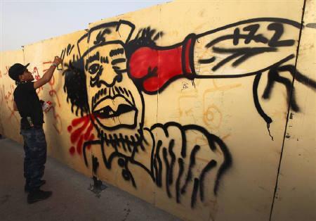 A painter paints a caricature of Libyan leader Muammar Gaddafi in Benghazi May 1, 2011. REUTERS/Mohammed Salem